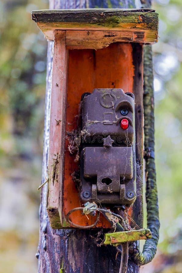 Imagem de uma caixa de controle suja velha com teias de aranha em um polo de madeira fotografia de stock