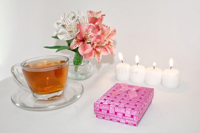 Imagem de uma caixa de presente luxuosa cor-de-rosa com um ramalhete de flores bonitas do Alstroemeria, de uma vela romântica e d imagem de stock royalty free