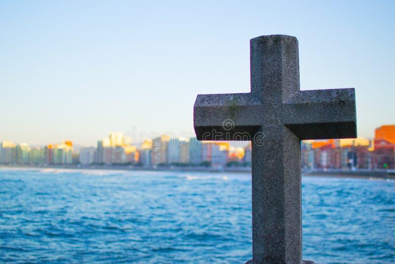 Imagem de uma cruz de pedra com o mar e de constru??es no fundo na praia de San Lorenzo, Gijon, as Ast?rias, Espanha imagens de stock royalty free