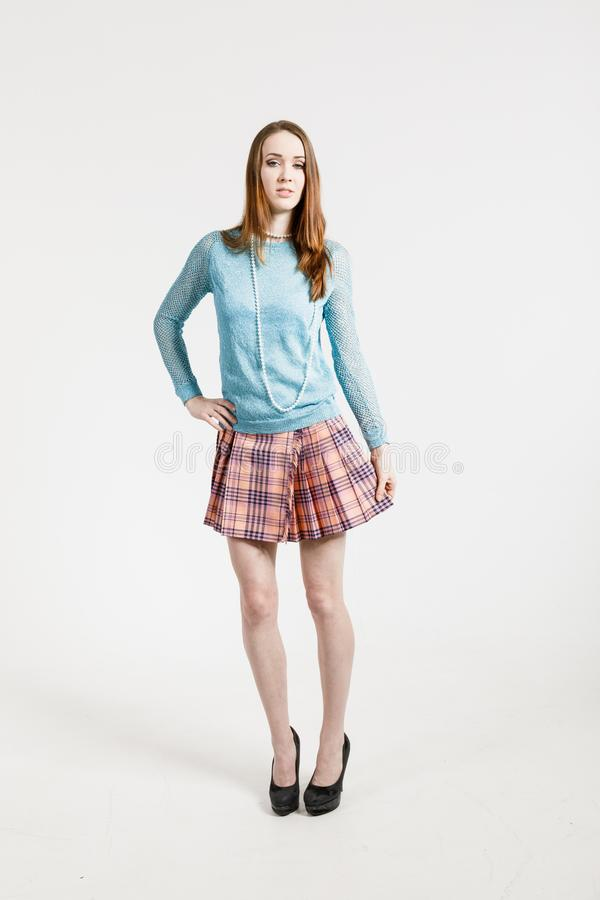 Imagem de uma jovem mulher que veste uma saia curto e um pulôver de turquesa fotos de stock royalty free