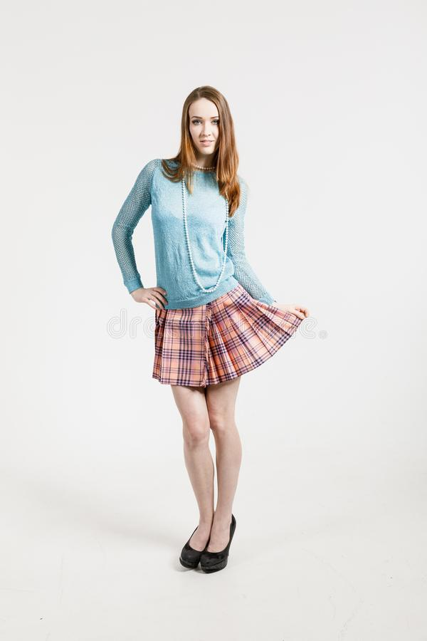 Imagem de uma jovem mulher que veste uma saia curto e um pulôver de turquesa fotografia de stock royalty free