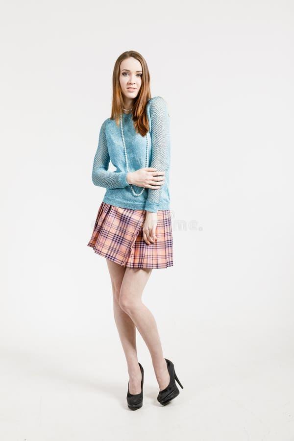 Imagem de uma jovem mulher que veste uma saia curto e um pulôver de turquesa imagem de stock