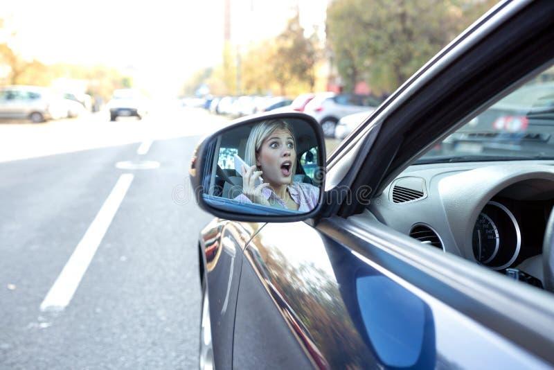 Imagem de uma mulher chocada no espelho da vista lateral imagens de stock