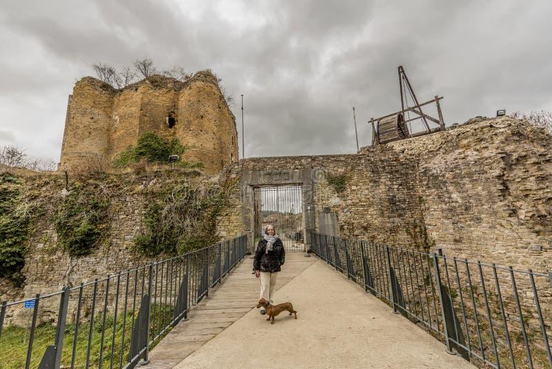 Imagem de uma mulher com seu cão na ponte que conduz à entrada do castelo Franchimont fotos de stock royalty free