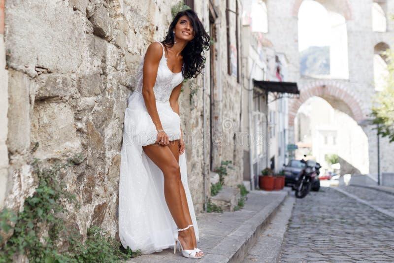 A imagem de uma noiva moreno lindo levanta sensual perto da cidade velha em greece, horas de verão Casamento em greece imagens de stock
