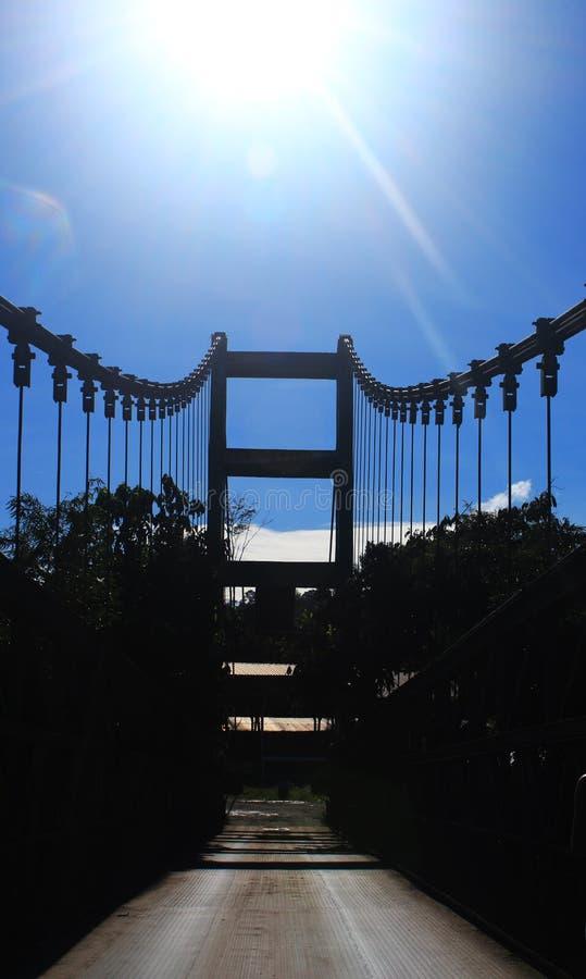 Imagem de uma ponte do metal que mostra uma fileira dos cabos e de um céu azul brilhante com o sol no céu imagem de stock