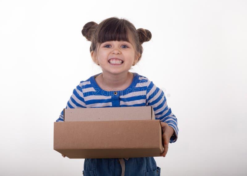 Imagem de uma posição feliz da criança com a caixa da encomenda postal isolada sobre o fundo branco imagens de stock royalty free