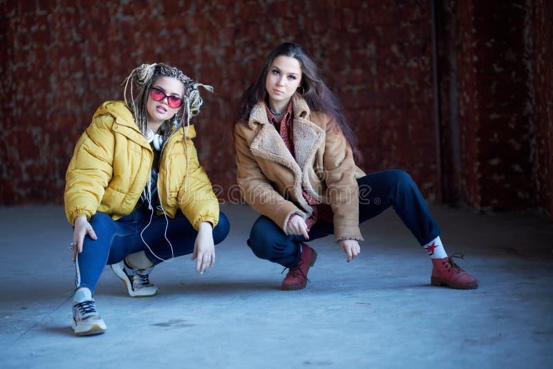 Imagem de uma posição feliz nova de dois amigos das mulheres sobre a parede olhando a c?mera imagens de stock royalty free