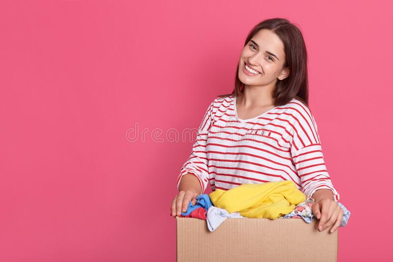 Imagem de uma senhora morena com uma aparência agradável, com caixa nas mãos contra a parede rosa, fazendo trabalho de caridade,  imagem de stock royalty free