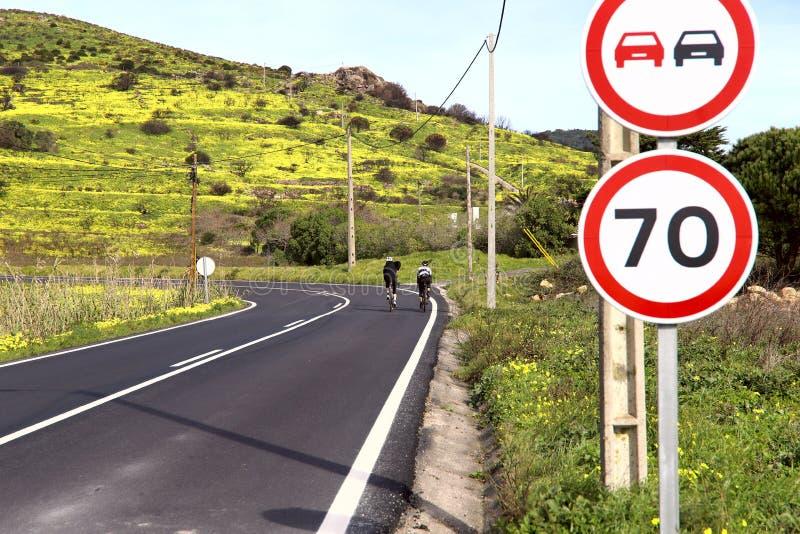 Imagem de uma superfície de estrada com uma volta afiada e de dois ciclistas na distância imagem de stock