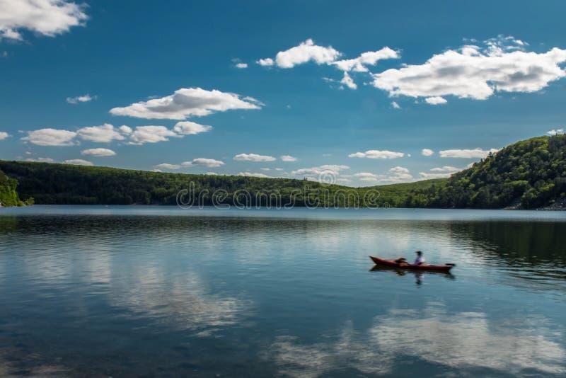Imagem de WI do lago devil, com o barco que flutua na água sob céus azuis, exposição longa fotos de stock royalty free
