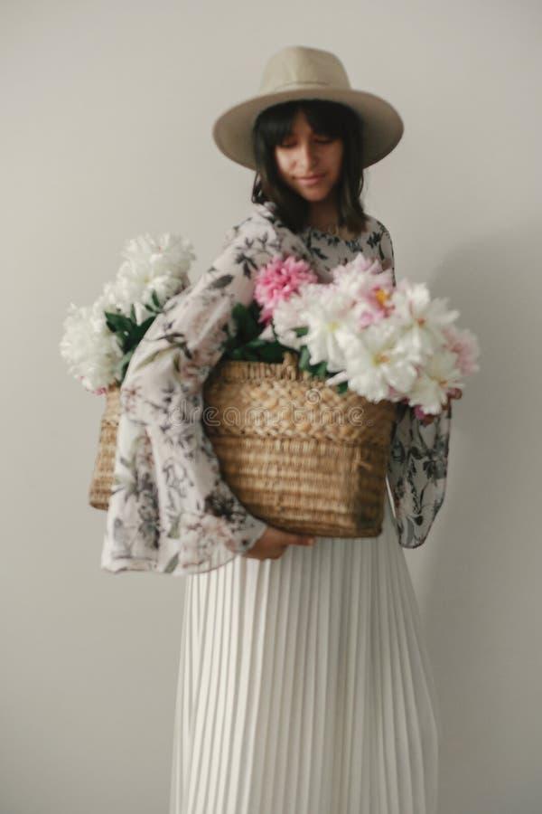 Imagem defocused borrada da menina do boho que guarda as peônias do rosa e as brancas na cesta rústica Mulher do moderno no chapé fotografia de stock royalty free