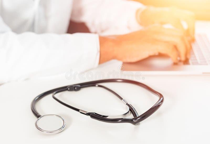 Imagem Defocused de um doutor que trabalha com o laptop no escritório médico do espaço de trabalho como o conceito com estetoscóp imagens de stock royalty free