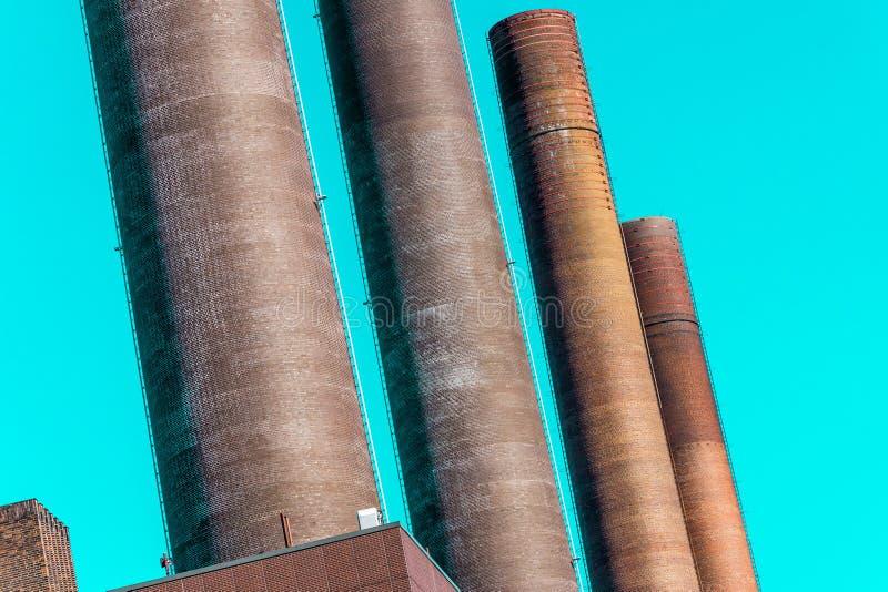 Imagem deliberadamente curvada do sumário das chaminés do central elétrica de uma grande planta industrial fotos de stock
