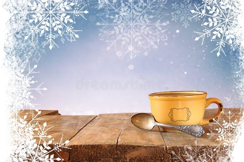 Imagem dianteira do copo de café sobre a tabela de madeira na frente do fundo do brilho com folha de prova do floco de neve imagem de stock royalty free