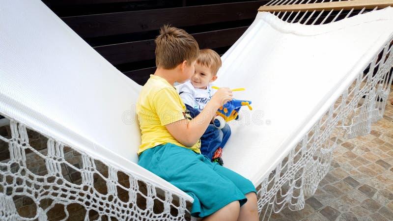 Imagem do adolescente que senta-se e que balança na rede com seu irmão mais novo mais novo no quintal da casa fotografia de stock royalty free