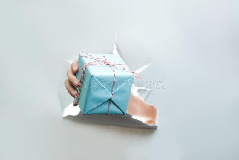A imagem do ano novo do Natal, presente quebra através do papel, com plac fotos de stock royalty free