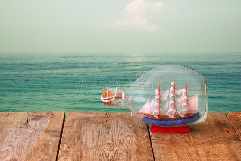 Imagem do barco decorativo na garrafa na tabela de madeira na frente do mar Conceito náutico imagem filtrada retro imagens de stock royalty free