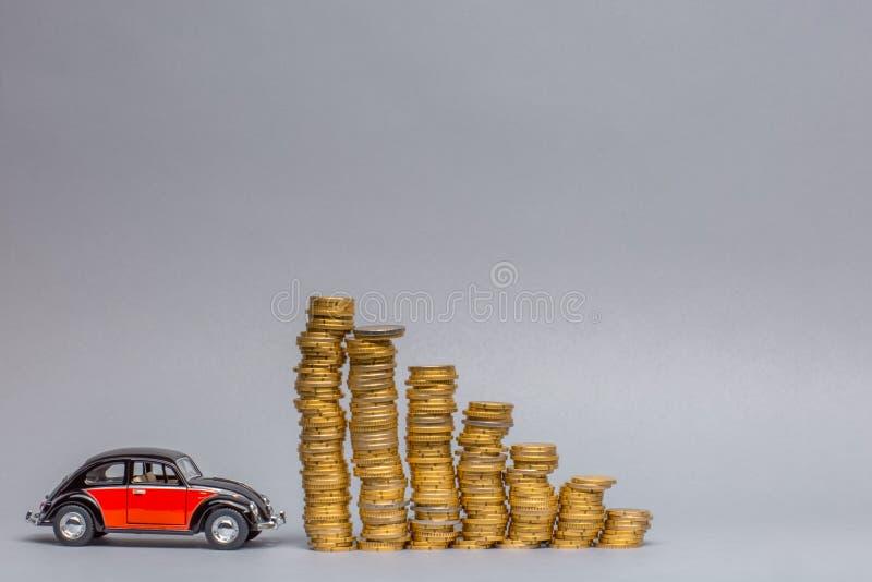 Imagem do carro de Crimson sentada ao lado de uma fileira de colunas de tamanho de moedas, sobre fundo cinza foto de stock royalty free