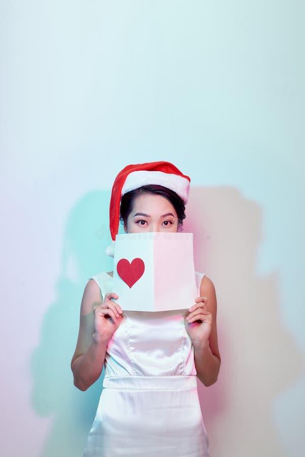 A imagem do cartão romântico da leitura fêmea bonita feliz com coração vermelho grande, mulher atrativa obteve o cartão sensual e fotografia de stock