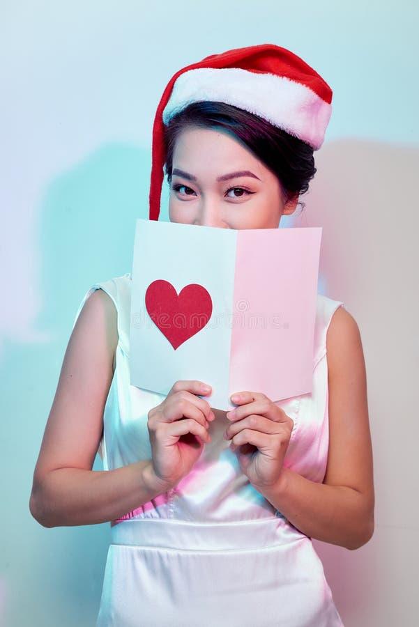 A imagem do cartão romântico da leitura fêmea bonita feliz com coração vermelho grande, mulher atrativa obteve o cartão sensual e fotografia de stock royalty free