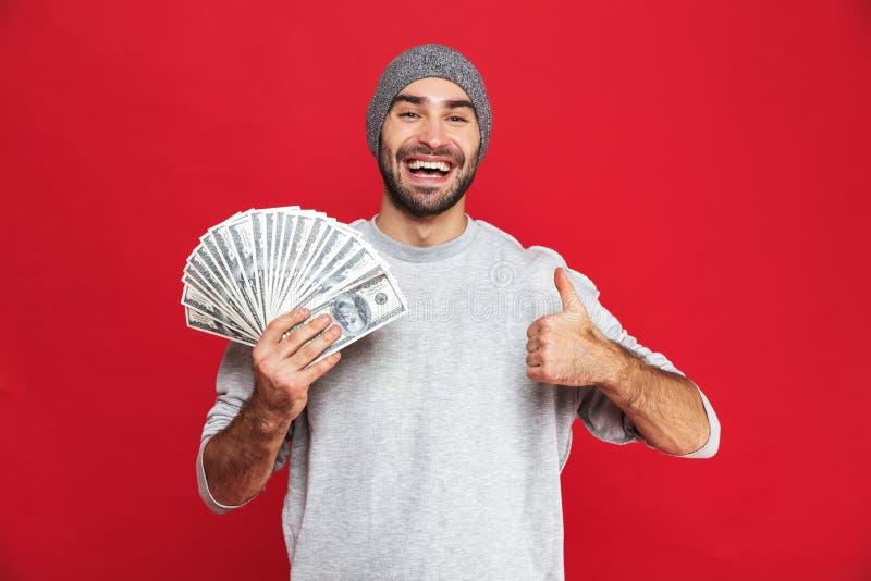 Imagem do chapéu vestindo europeu do homem 30s que guarda o fã do dinheiro, isolada sobre o fundo vermelho imagem de stock