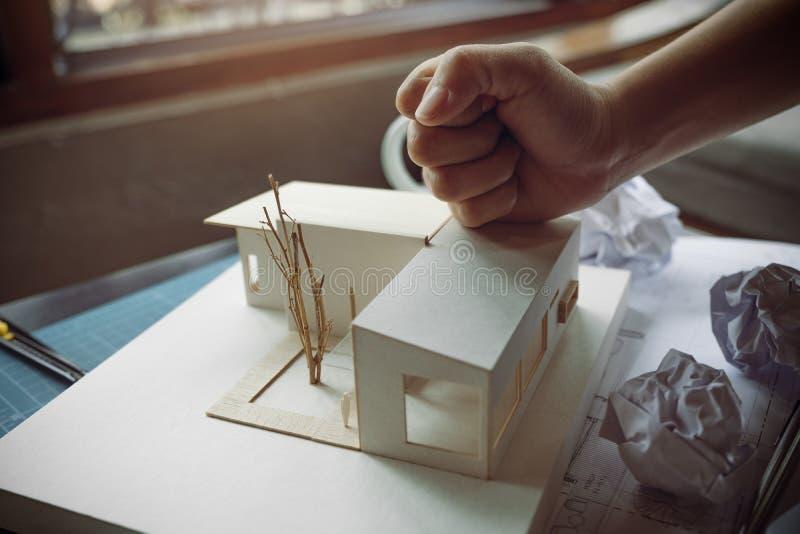 A imagem do close up do arquitetos irritados tenta destruir um modelo da arquitetura na tabela foto de stock