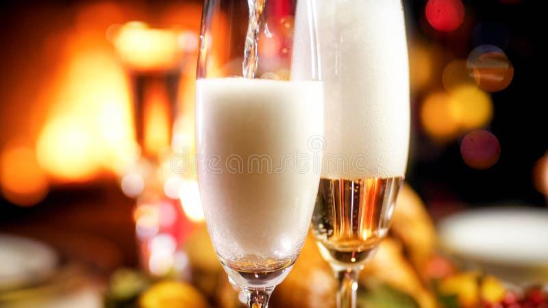 Imagem do close up do champanhe de derramamento nos vidros no jantar de Natal romântico imagem de stock