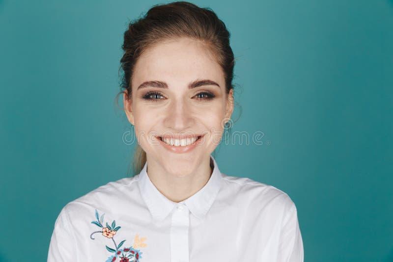 Imagem do close up da jovem mulher considerável que levanta em um estúdio isolado sobre o fundo azul foto de stock