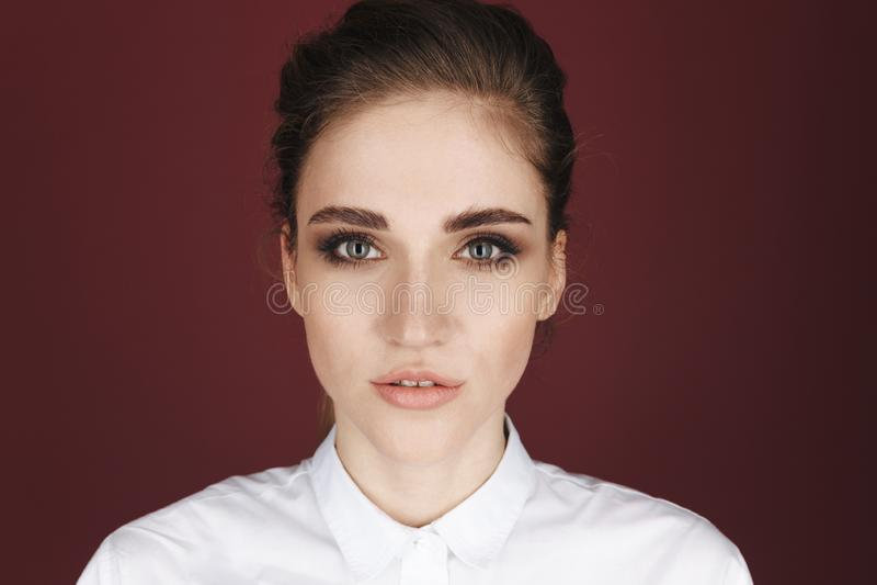 Imagem do close up da jovem mulher considerável que levanta em um estúdio isolado sobre o fundo cor-de-rosa escuro imagens de stock royalty free