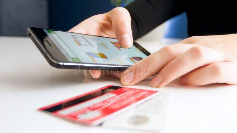 Imagem do close up da jovem mulher que faz a ordem em linha no smartphone e que paga com cartão de crédito foto de stock