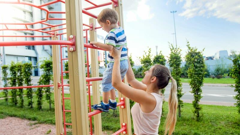 Imagem do close up da mãe nova que ajuda seu filho pequeno que escala em escadas do metal alto no campo de jogos das crianças dos fotografia de stock royalty free