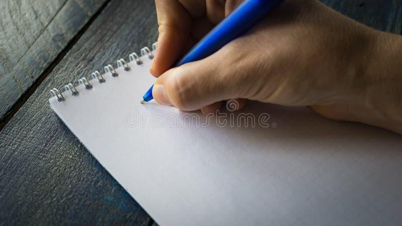 Imagem do close up da mão que escreve para baixo em uma placa A ideia superior das mãos fêmeas que fazem algumas anotações trabal fotografia de stock