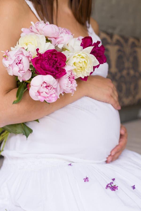 Imagem do close-up da mulher gravida no vestido branco agradável que toca em sua barriga com mãos e que guarda um ramalhete das p fotos de stock royalty free