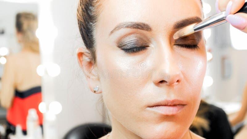 A imagem do close up da pintura do maquilhador modela os olhos com escova fotos de stock