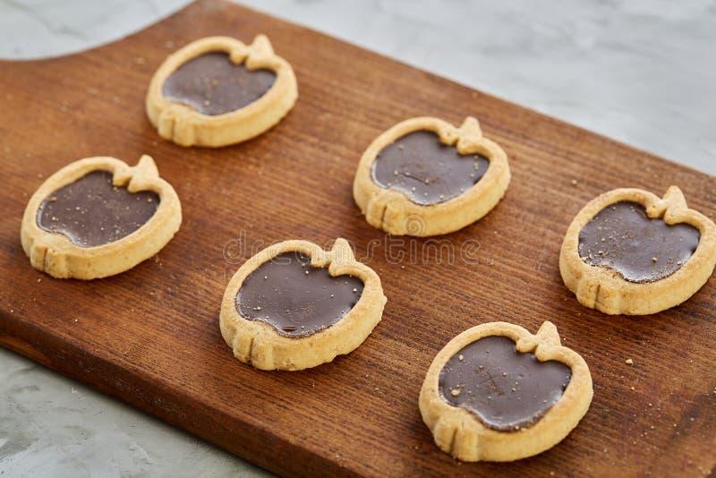 Imagem do close-up da vista superior de cookies pomiformes saborosos na placa de corte, profundidade de campo rasa, foco seletivo fotos de stock royalty free