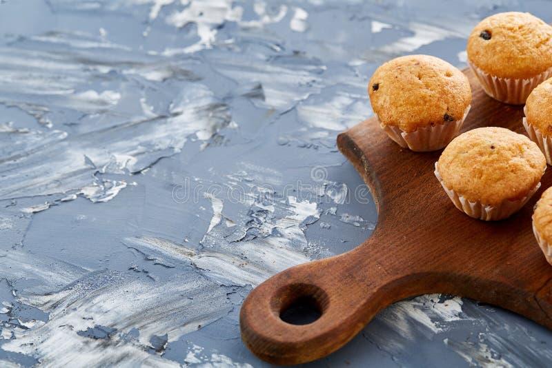 Imagem do close-up da vista superior de queques saborosos na placa de corte, profundidade de campo rasa, foco seletivo imagem de stock