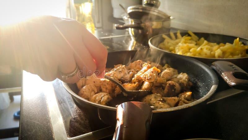 Imagem do close up das ferramentas fêmeas da cozinha da terra arrendada da mão que fritam a carne na frigideira contra raios de l foto de stock royalty free