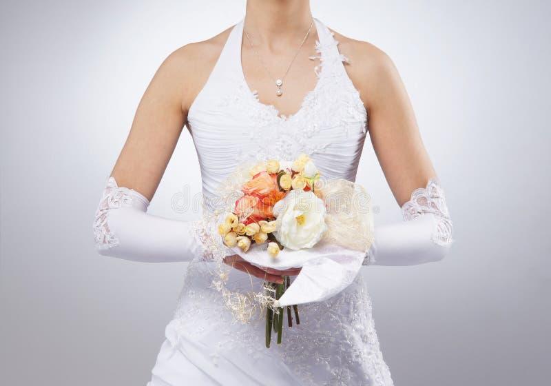 A imagem do close-up das flores realizou nas mãos da noiva fotos de stock