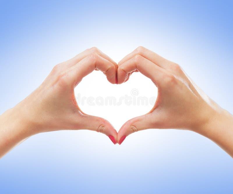 Imagem do close-up das mãos fêmeas em uma fôrma de um coração imagens de stock royalty free