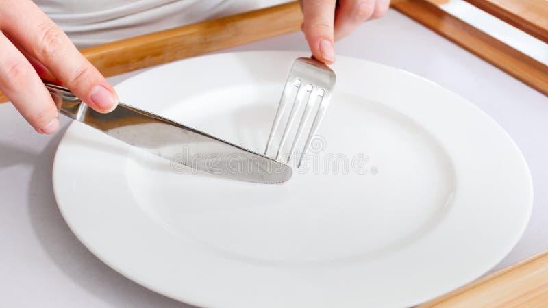 Imagem do close up das mãos fêmeas que guardam a forquilha e a faca no prato vazio Conceito da dieta e do peso do afrouxamento imagens de stock