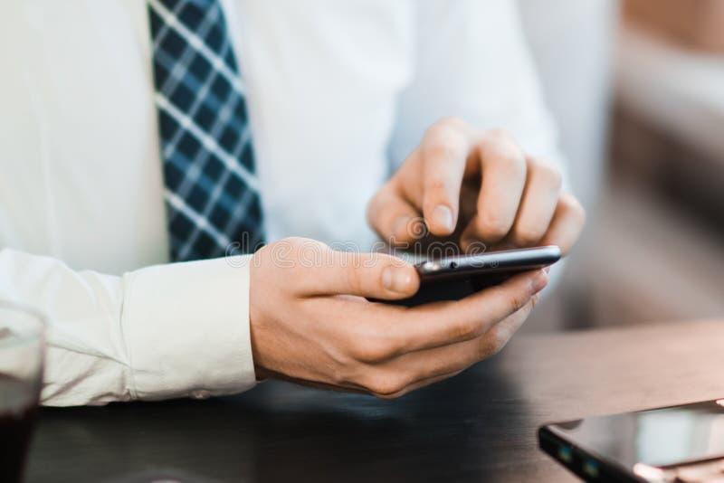 Imagem do close-up das mãos masculinas usando o smartphone na noite na rua da compra da cidade, na pesquisa ou no conceito social fotografia de stock