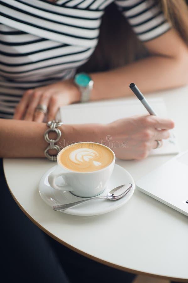Imagem do close-up das mãos que fazem anotações no papel, no copo do cappucciono e no portátil que está em uma tabela em um café foto de stock