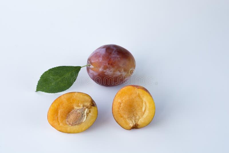 Imagem do close-up de ameixas suculentas maduras em um fundo branco imagens de stock