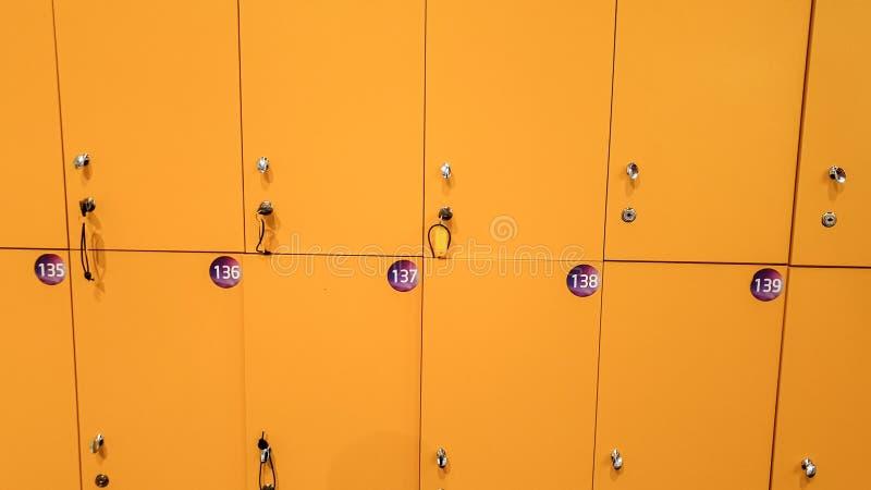 Imagem do close up de fileiras longas retas de cacifos amarelos na escola ou na faculdade imagem de stock royalty free