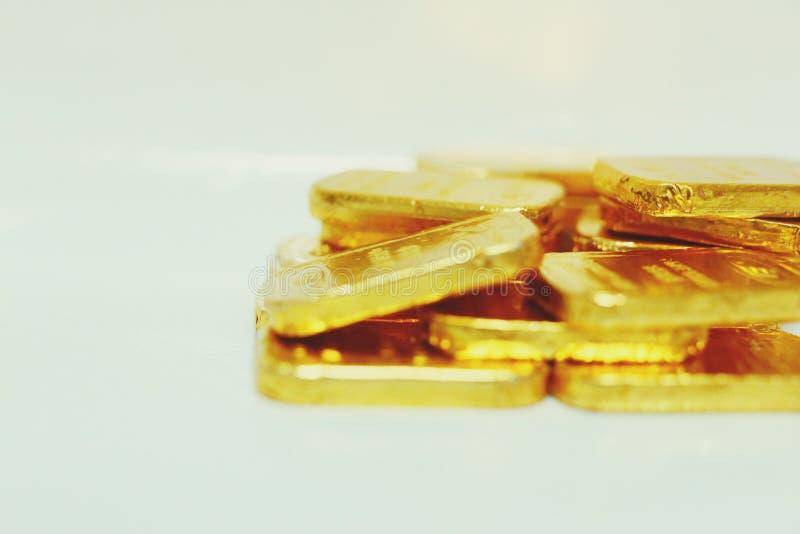 Imagem do close-up de muitas barras de ouro que centram-se sobre o fundo branco de salvamento do ouro do ouro do fantoche do neg? imagem de stock