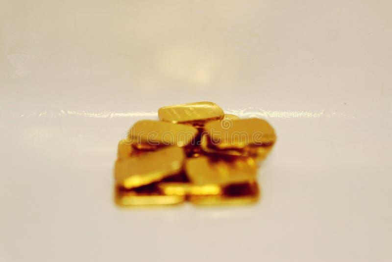 Imagem do close-up de muitas barras de ouro que centram-se sobre o fundo branco de salvamento do ouro do ouro do fantoche do neg? imagem de stock royalty free