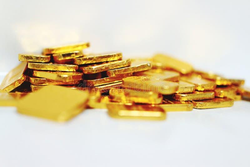 Imagem do close-up de muitas barras de ouro que centram-se sobre o fundo branco de salvamento do ouro do ouro do fantoche do neg? foto de stock