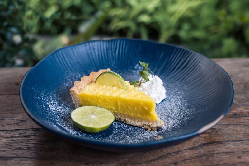 Imagem do close up de um bolo amarelo do coalho de limão na placa cerâmica azul na tabela de madeira com natureza verde imagens de stock
