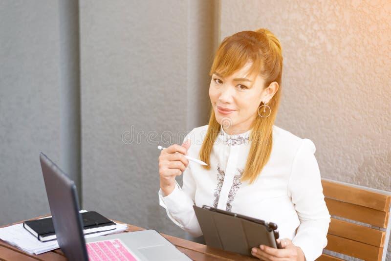 Imagem do close up de uma mulher de negócio asiática bonita que realiza e que usa o PC da tabuleta no café foto de stock